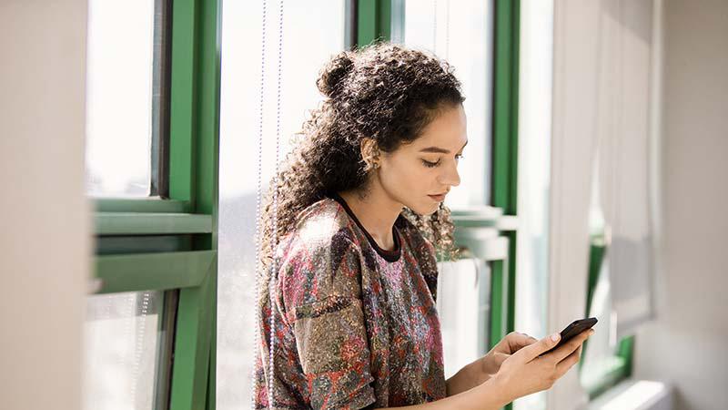صورة امرأة تحمل هاتفًا.