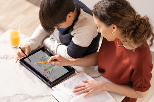 طفل ذكر يعمل على كمبيوتر لوحي بينما ينظر أحد والديه الأنثى فوق كتفه
