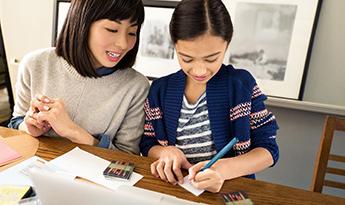أم وابنتها تعملان على الواجبات المنزلية