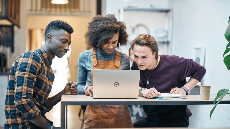 ثلاثة أشخاص بالغين ينظرون إلى شاشة كمبيوتر محمول