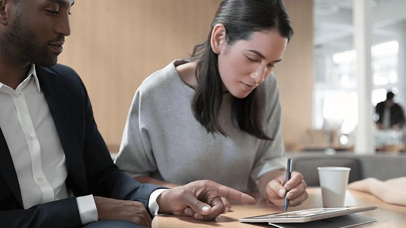 امرأة ورجل يعملون معاً على كمبيوتر لوحي Surface.