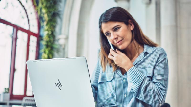 صورة لسيدة تعمل على كمبيوتر محمول وهاتف. ارتباطات إلى Answer Desk لذوي الاحتياجات الخاصة.