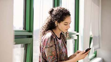 صورة لامرأة واقفة بجانب نافذة وتستخدم هاتف