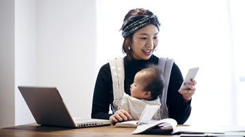 سيدة يابانية مبتسمة تحمل طفلها في حمالة أطفال بينما تفحص هاتفها وتعمل من كمبيوتر محمول