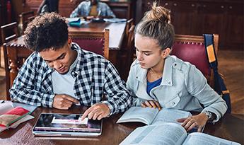 اثنين من الطلاب يدرسون في مكتبة