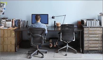 صورة لشخص يجلس على مكتب، ويعمل على جهاز كمبيوتر.