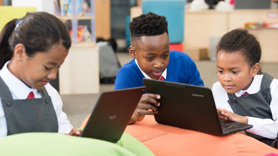 صورة لأطفال في المدرسة وهم يعملون على أجهزة كمبيوتر محمولة