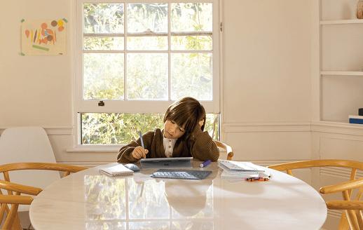طفل يستخدم جهاز كمبيوتر لوحي وهو يجلس على طاولة.