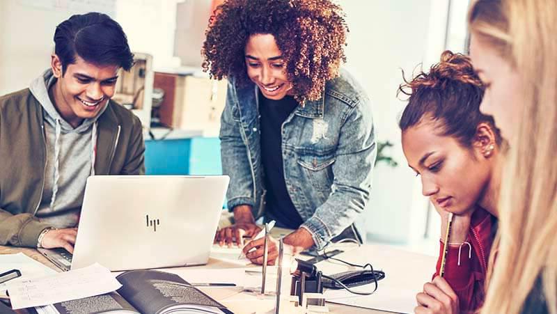 أربعة طلاب في المرحلة الثانوية أو الجامعية يعملون على مشروع باستخدام كمبيوتر محمول والكتب