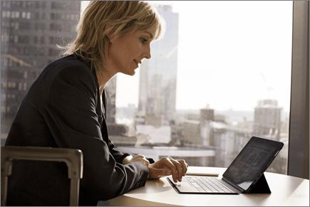 سيدة أعمال تعمل على جهاز كمبيوتر محمول في مكتب بعيد