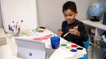 يستخدم طفل صغير الرسامات على الورق بينما يشاهد كمبيوتر Surface محمولا ومفتوحا