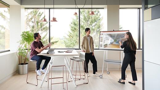 يظهر مجموعة من 3 أشخاص مجتمعين حول Surface Hub 2S لعقد اجتماع مخصص.