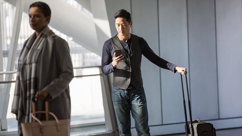 رجل في مطار يستخدم الهاتف وسيدة تمر بجواره