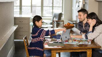 صورة لعائلة على طاولة مطبخ يعملون على جهاز كمبيوتر