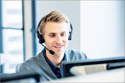 صورة لرجل ينظر إلى جهاز كمبيوتر ويرتدي سماعة رأس.