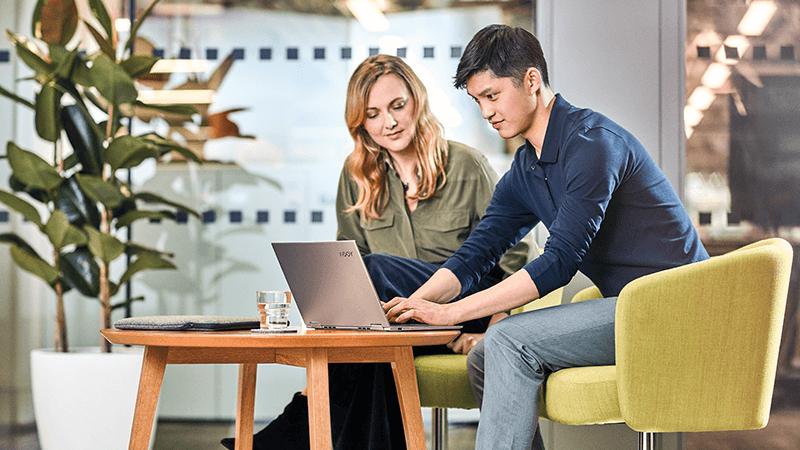رجل وامرأة يعرضون شيء ما معاً على كمبيوتر محمول.