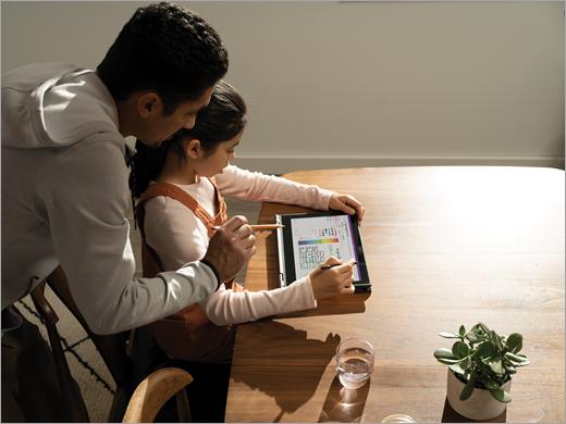 يساعد الأب ابنته على العمل على كمبيوتر لوحي في دفتر ملاحظات للصف