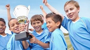 снимка на деца в спортния екип, празнуващ победа и държащ трофей