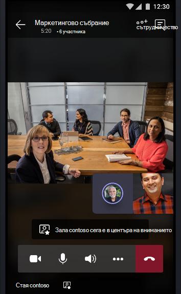 Изображение на онлайн събрание на екипи с конферентна зала, пълна с хора, които разговарят с двама други участници в събранието.