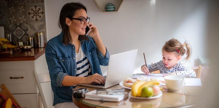 fotka rodiče na telefonu s dítětem v blízkosti
