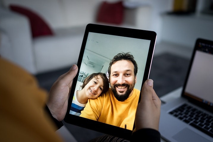 fotka osoby, která drží tabletové zařízení s videohoněm