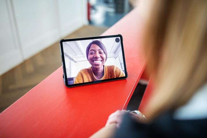 fotka osoby používající tablet s videokonferencemi