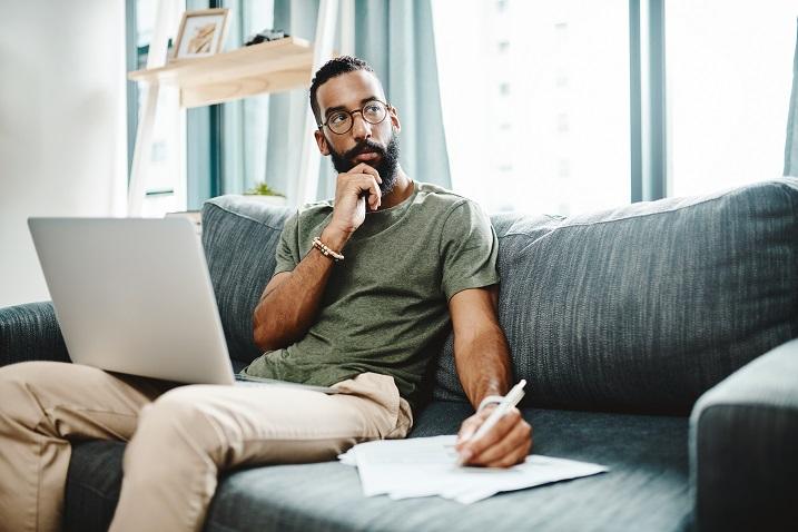 fotka muže sedící na pohovce s papírem a přenosným počítačem