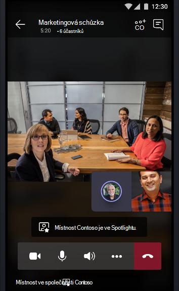 Obrázek online schůzky v Teams s konferenční místností plnou lidí, kteří mluví ke dvěma dalšími účastníky schůzky.