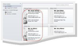 Forretningskontakter i Outlook-mappen Kontakter. Oplysninger for hver kontakt vises som visitkortvisning. Der er en rød stiplet linje omkring to forretningskontakter.