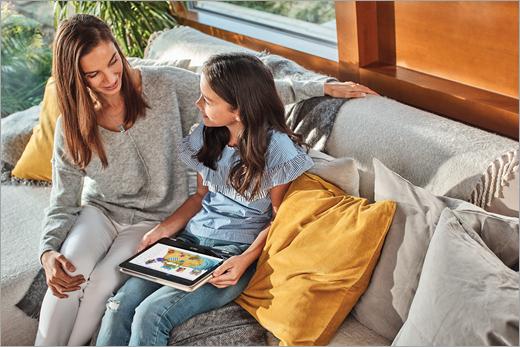 En mor og hendes datter sidder i en sofa, som datteren bruger Paint 3D på en bærbar computer