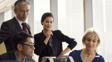 Viser en gruppe af personer, der holder møde i et mindre mødelokale i en høj kontorbygning.