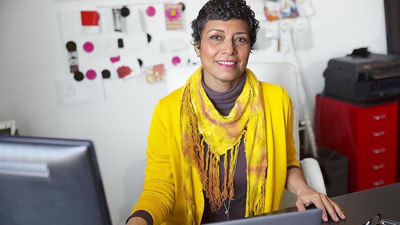 En kvinde, der sidder ved en computer på et kontor