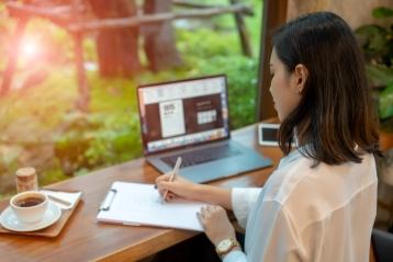 En kvinde, der skriver et brev tæt på sin bærbare computer
