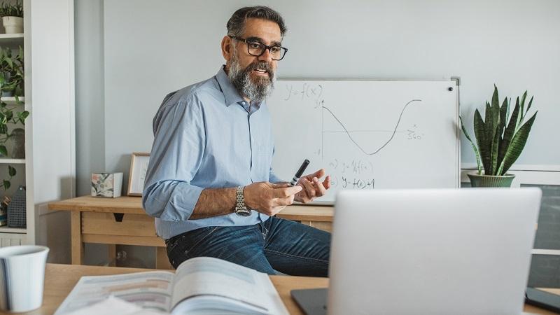 Billede af en lærer ved en bærbar computer med en tavle i baggrunden.
