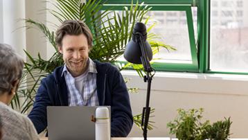 En yngre mand vist i mindre virksomhed med bærbar computer på moderne arbejdsplads.