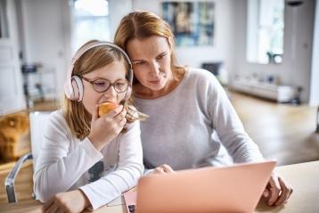 En mor og en datter, der kigger på en PC