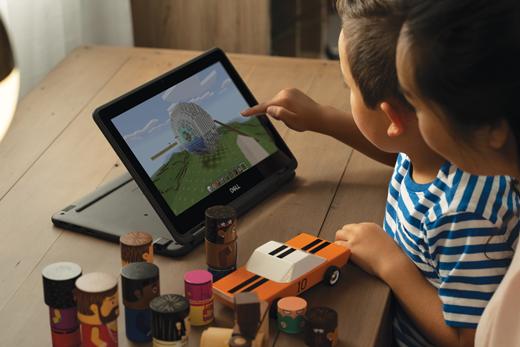 En ung drenge bruger Minecraft på en bærbar computer, mens en kvinde ser ham over skulderen