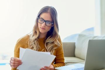 En kvinde med briller, der gennemgår papirer