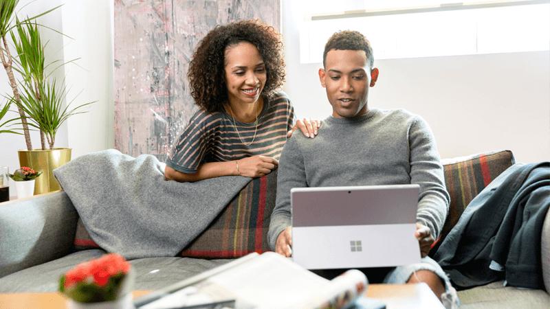 Mand, der sidder i en sofa og kigger på en bærbar computer, og en kvinde, der står bag sofaen og ser ham over skulderen