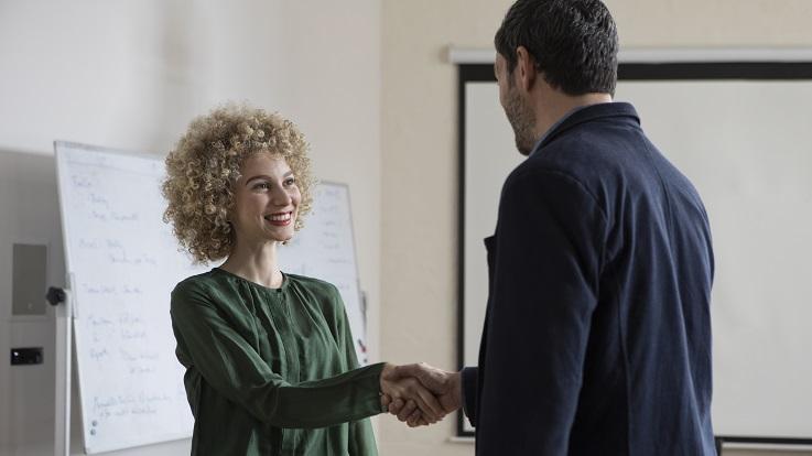 Foto einer Frau und eines Mannes, der in einem Konferenzraum die Hände schüttelt.