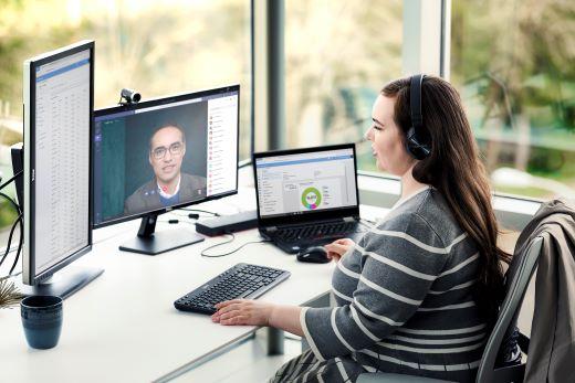Frau an einem Schreibtisch mit Monitor mit Teams-Besprechung.