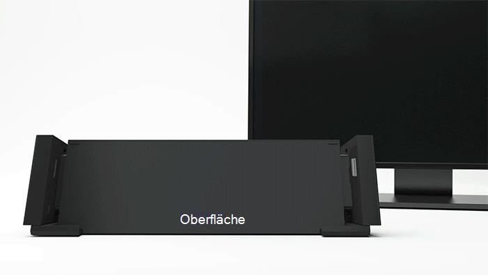 Animierte Grafik mit einem Surface-Gerät, das in eine Dockingstation geschoben wird, sowie einem Monitor hinter dieser Dockingstation, auf dem dasselbe Bild wie auf dem Surface angezeigt wird