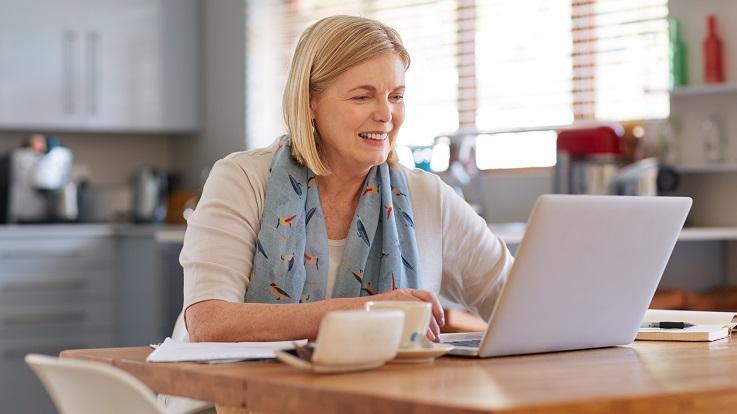 Foto einer Frau an einem Küchentisch, die eine E-Mail auf einem Computer liest