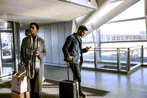 Personen auf einem Flughafen, die Ihre mobilen Geräte überprüfen.