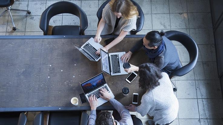 Aufsichtfoto von vier Personen, die an einem Tisch an Computern und Geräten arbeiten