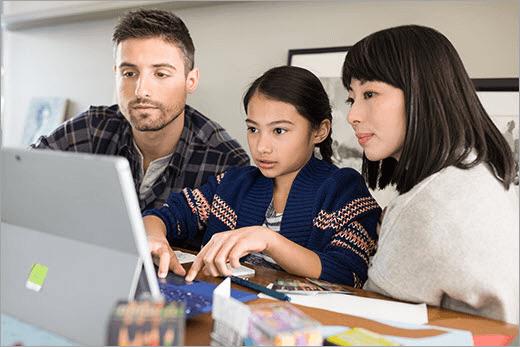 Zwei Erwachsene und ein Kind betrachten einen Laptop