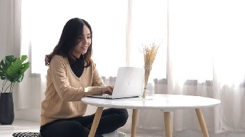Photo of a woman siting at a table with a laptop.