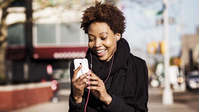 A woman with earbuds and a smartphone