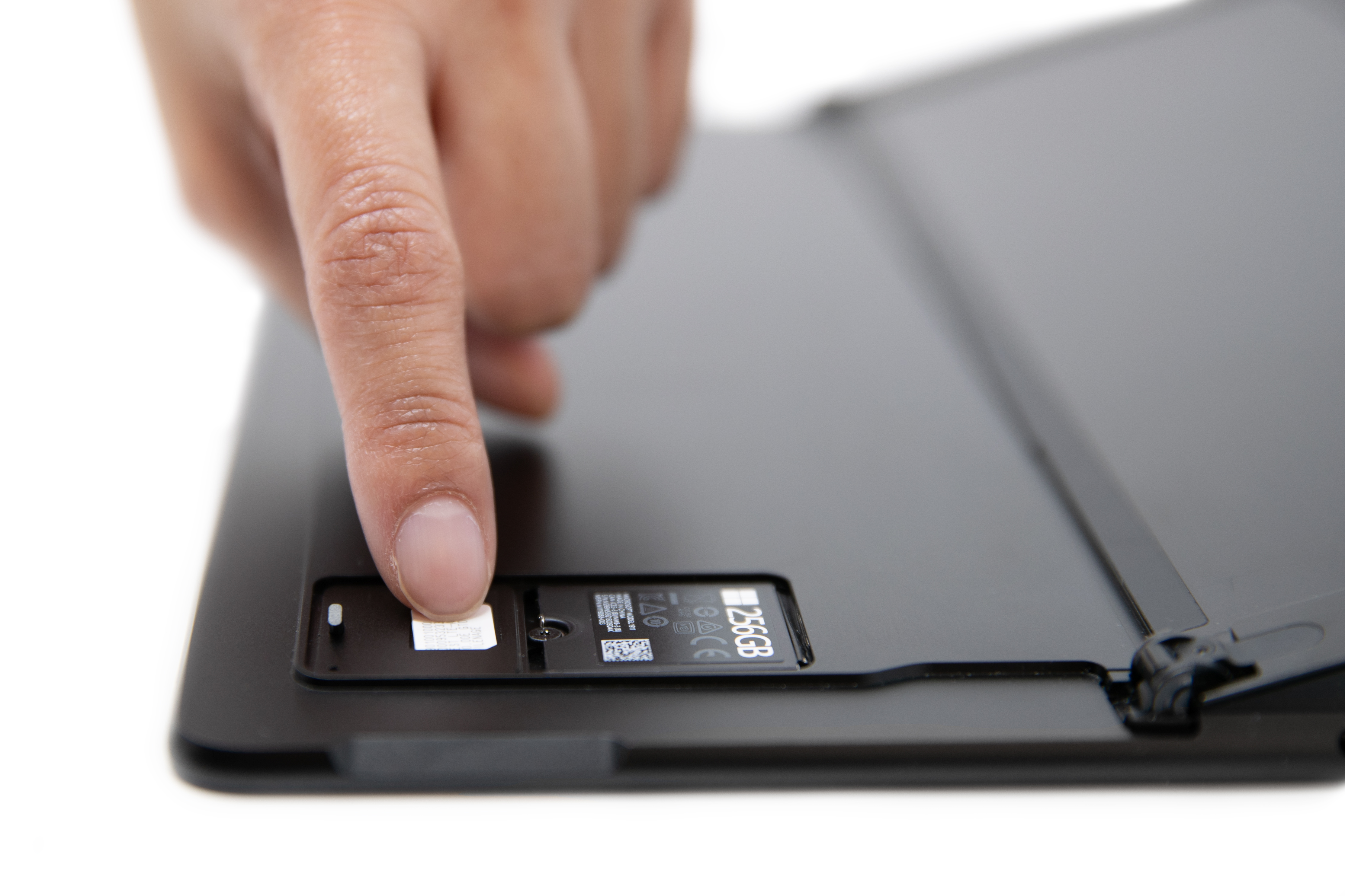 A person sliding in a SIM card into the Surface Pro X SIM slot.