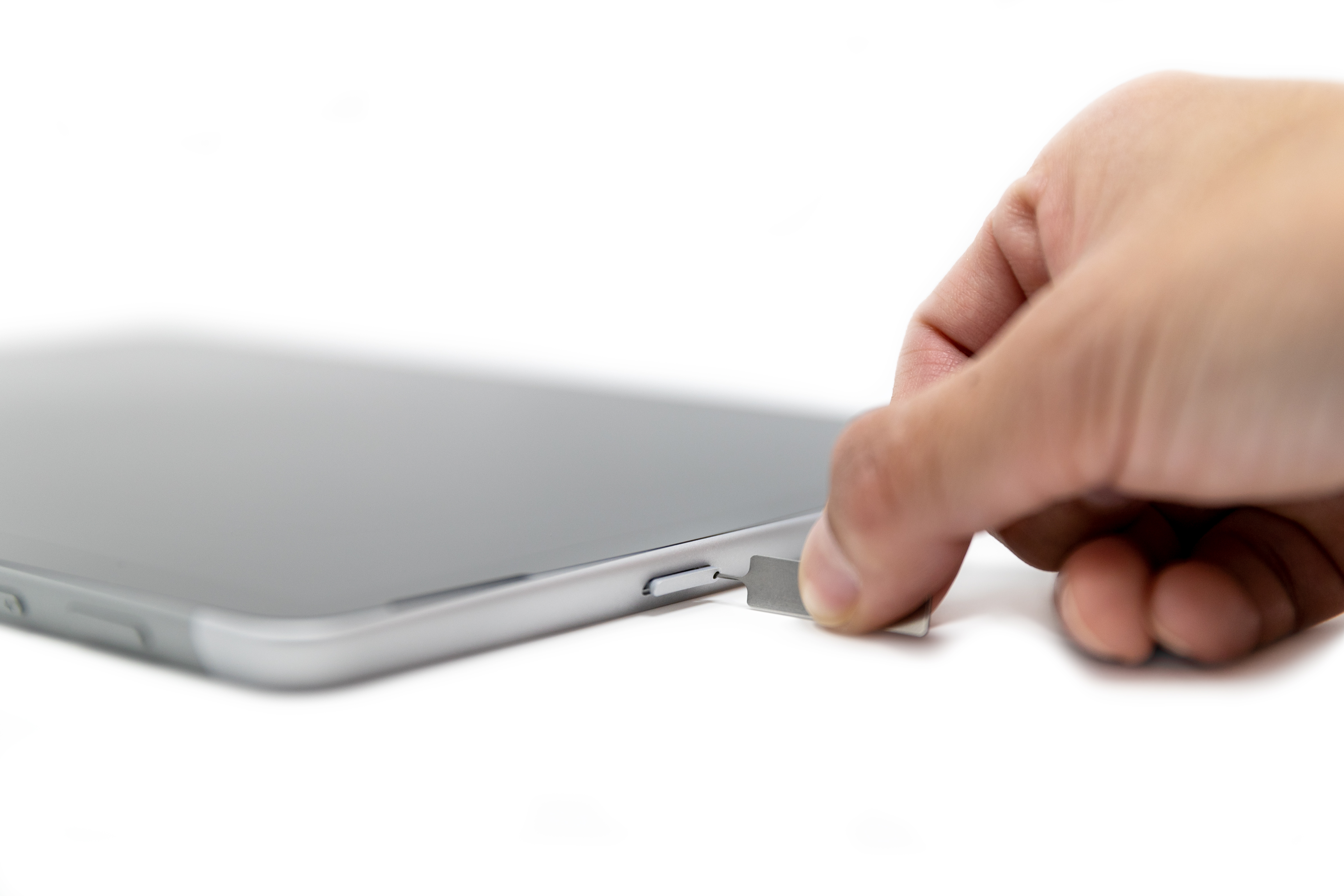 A person inserting a SIM pin into the SIM card slot of a Surface Go 2.